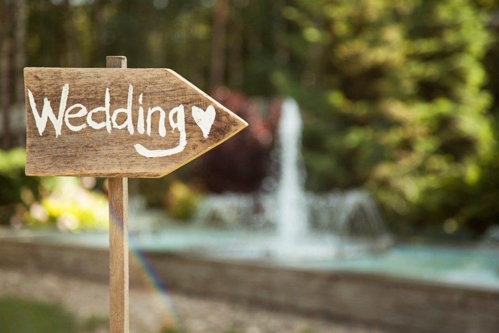 Wedding decor. Wooden plaque with the inscription Wedding. Wedding on a plate green background and a fountain. Wedding decorations,